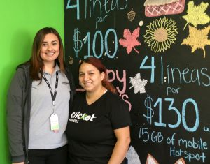 Vanessa Valenzuela (left) and Beatrice Lee, sales associates at Cricket Wireless in Holtville, in front of a list of the store's Black Friday discounts on Nov. 29.